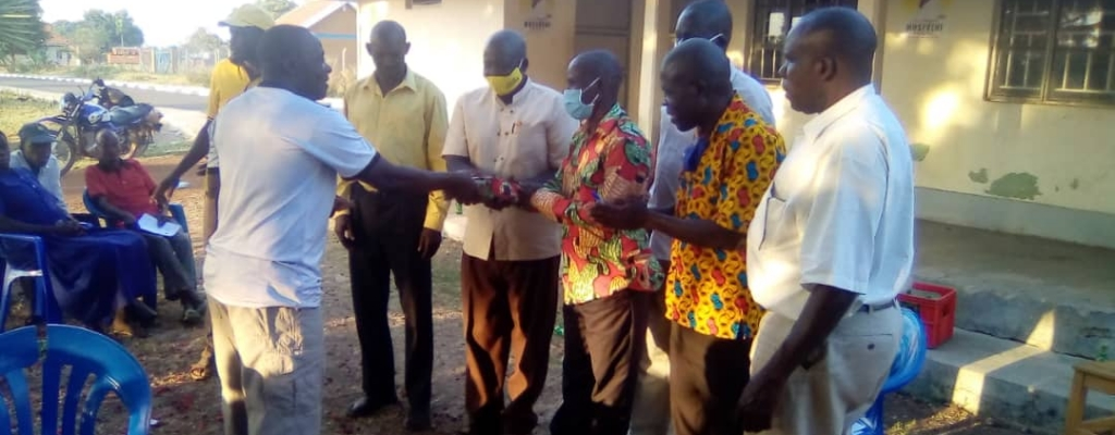 The district officials of Kapelebyong handing over EMYOOGA money to the Constituency SACCO beneficiaries